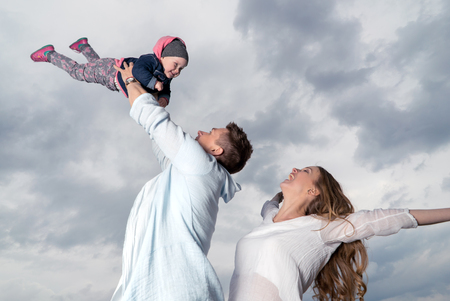 feelings and emotions: Happy family. Young father throws up baby in the sky. Positive human emotions, feelings.