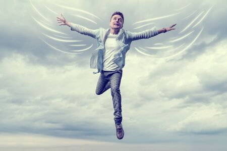 flying man: Young man with drawn wings flying in sky background