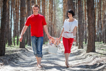 Happy family with child in backet walking at bright summer day