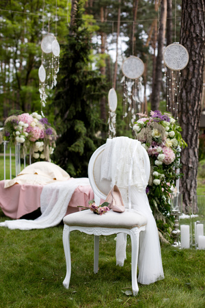 Beautiful wedding shoes with high heels and a bouquet of colorful flowers on a vintage chair on the nature in sunset light, decorations, preparing for the wedding, details, boudoir Standard-Bild