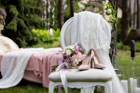 Beautiful wedding shoes with high heels and a bouquet of colorful flowers on a vintage chair on the nature in sunset light, decorations, preparing for the wedding, details, boudoir Stockfoto