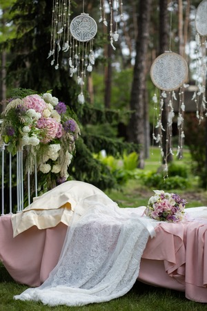 Beautiful wedding bouquet of colorful flowers on a vintage bed on the nature in sunset light, decorations, preparing for the wedding, details, boudoir Stockfoto