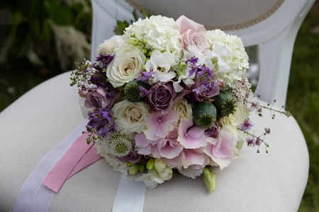 Beautiful wedding bouquet of colorful flowers on a vintage chair Standard-Bild