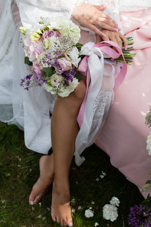 negligee: Beautiful female bare feet in the bridal negligee. Bride putting a wedding bouquet on his feet Stock Photo