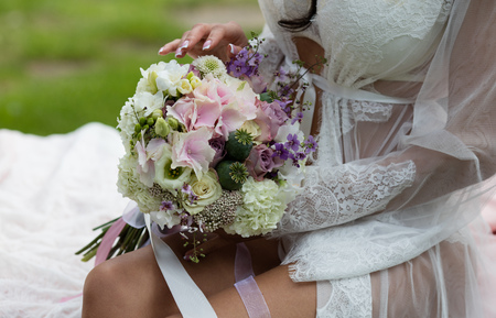 Beautiful female bare feet in the bridal negligee. Bride putting a wedding bouquet on his feet Stockfoto