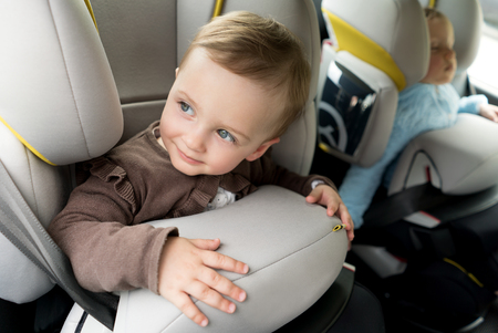 Small children in car seats in the car