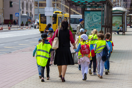a group of students, led by a teacher, go through the city in reflective vests