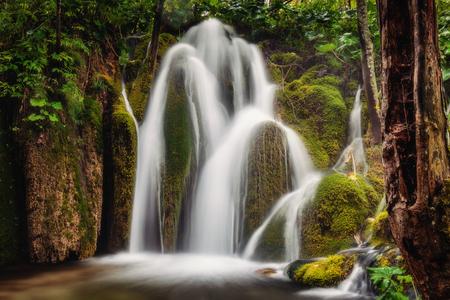 Long exposure waterfall over brown and green rocks shot in low key at Plitvice lakes,Croatia. Stok Fotoğraf