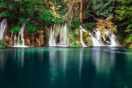 Long exposure waterfall falling to emerald lake at Plitvica, Croatia.