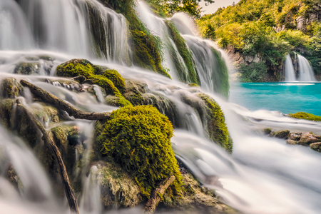 Silk waterfall shot with long exposure over brown rocks with blue pond at Plitvice lakes, Croatia.