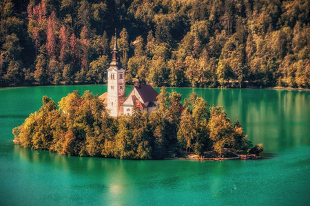Island at the middle of Bled lake with a small church and reflection. Stock Photo