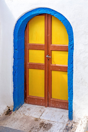 Blue yellow and brown door  with white wall in Santorini, Greece.