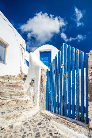 A very traditional alley view of the architecture in Oia, on the greek island Santorini, Greece. A blue door, fence and windows of a whitewashed house against the blue sky. Stock Photo