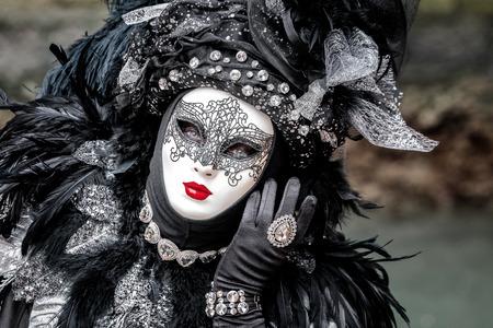 Máscara negra del carnaval que lleva el sombrero con las plumas largas, los labios rojos y el tracery delicado, Venecia, Italia. Foto de archivo - 76714631