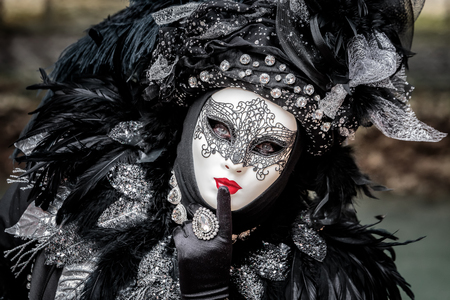 Black carnival mask wearing hat with long feathers, red lips and delicate tracery, Venice, Italy.