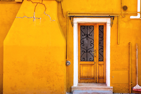 Picturesque door on yellow wall of houses on the famous island Burano, Venice, Italy