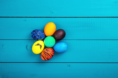 Coloful Easter eggs shot on blue wooden background. Stock Photo