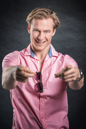 hait: Smiling modern man with blonde hait, pink shirt, stylish glasses pointing at viewer.