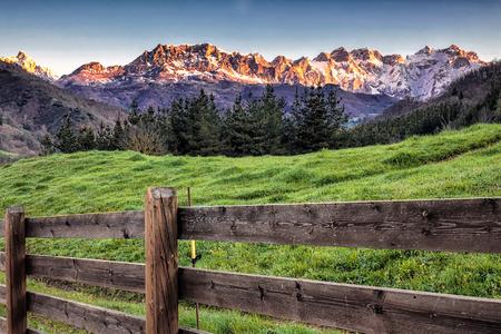 Salida del sol sobre picos de Europa cresta con valla de madera, Cantabria, España. Foto de archivo - 76240788