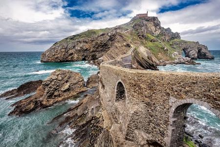 San Juan de Gaztelugatxe es una iglesia dedicada a Juan el Bautista conectada al continente por un puente artificial, Bermeo, País Vasco, España. Foto de archivo - 76242389