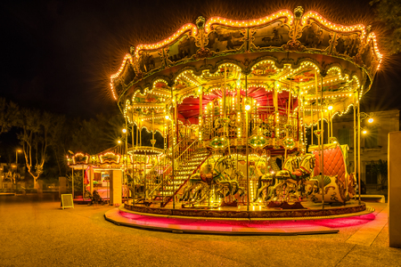 Brightly illuminated traditional carousel in Paris France at night.