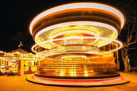 play the old park: Brightly illuminated traditional carousel in Paris France at night.