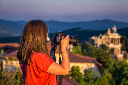 Girl taking of areal view photo at the sunset from high mountain of the Signaghi, Georgia. Stock Photo