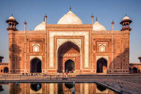 View of Taj Mahal with pool reflection in Agra India at sunrise.
