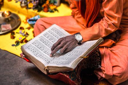 Old sadhu hand wearing hand watch pointing at line of holy book Varanasi, India. Stock Photo