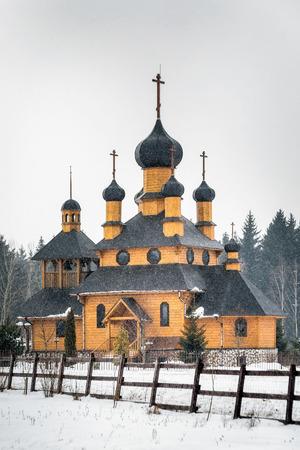 Wooden church under heavy snow in Dudutki, Belarus, 25 kilometers away from Minsk.