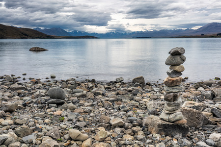 Balanced stone pyramid on shore near Church of the Good Shepherd at lake Tekapo, New Zealand. Summer landscape in New Zealand.