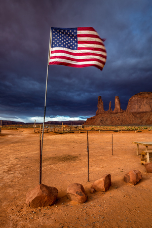 American flag flutters in the wind with storm in the background at Monument Valley, Arizona, USA.
