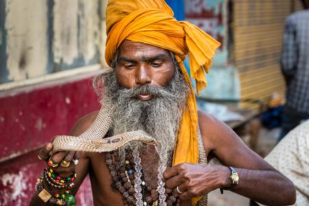 VARANASI, INDIA - MARCH 18, 2017: Holy man holding dangerous cobra snake in Varanasi, India. 新聞圖片