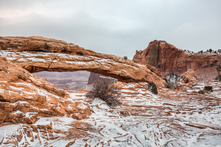 Classic view of famous Mesa Arch, symbol of the American Southwest, illuminated in scenic golden morning light at sunrise on a beautiful winter day in winter after heavy snow, Canyonlands National Park, Utah, USA