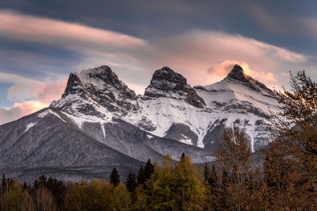 Sunset light just hitting the top of the Three Sister peaks near Canmore, Alberta, Canada Banco de Imagens - 113999910