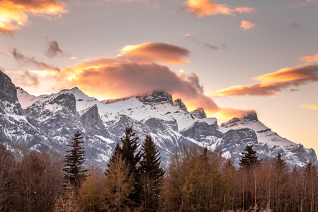 Sunset light just hitting the top of the Three Sister peaks near Canmore, Alberta, Canada