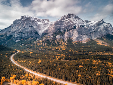 Kananaskis provincial park with lake, road, mountains and yellow autumn colored trees, Canada. Stock Photo