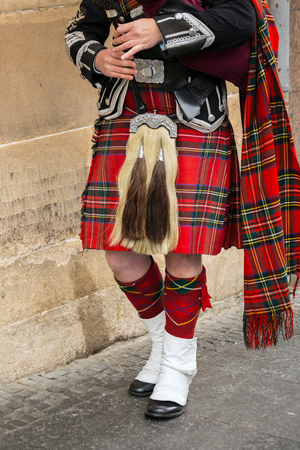 Scottish bagpiper dressed in traditional red and black tartan dress stand. Stock Photo