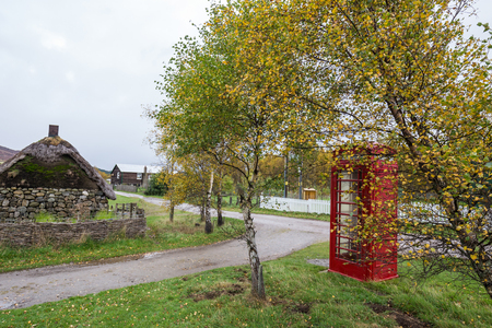 Beautiful phone booth in the village in Scotland, cloudy weather outside