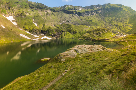 House on the lake in a very beautiful and picturesque place in the mountains near the famous Transfagaras highway in Romania Reklamní fotografie
