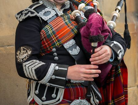 Edinburgh Scotland - October 10 2017: Scottish bagpiper dressed in traditional red and black tartan dress stand. Edinburgh - Scotland