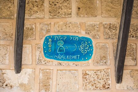 Tel Aviv, Israel - April 20 2018: Vintage tables with street names and ornaments on ancient stone houses in the old city of Jaffa in a warm Tel Aviv