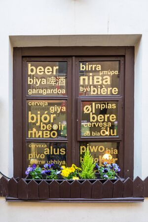 Vilnius, Lithuania - 13 April 2018: Window with inscriptions in different languages ​​around the world in a flowerpot blooming bright spring flowers in Vilnius
