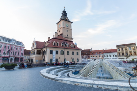 On the square in the old town there is a working fountain and a lot of beautiful and restored architecture in the city of Brasov in Romania Stock Photo