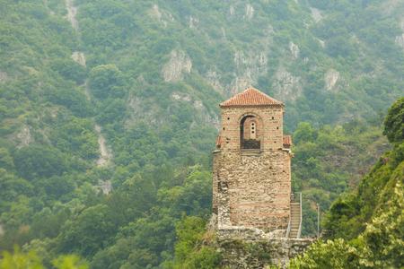 Una vecchia torre alta si erge sulle montagne in Bulgaria, intorno è molto verde e fuori fa bel tempo