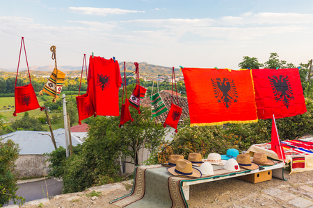 Various traditional Albanian souvenirs are sold on the market in a beautiful location overlooking the mountains