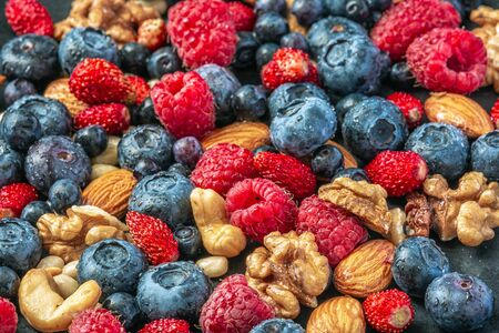 Close up shot of fresh variety of wild berries and nuts, healthy lifestyle.