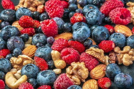 Primer plano de variedad fresca de frutos secos y bayas silvestres, estilo de vida saludable.