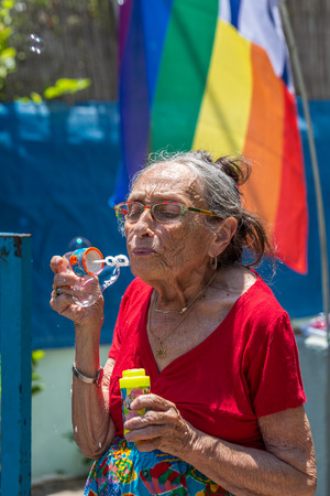 Tel Aviv, Israel - June 14 2019: Eldery woman blows soap bubbles at 21th annual Tel Aviv Pride Week. At the parade, people walking, dancing, singing, waving banners and rainbow flags celebrating the largest LGBT event in the middle east.
