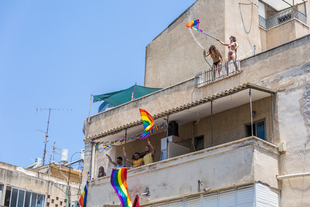 Tel Aviv, Israel - June 14 2019: People spray water from balcony at 21th annual Tel Aviv Pride Week. At the parade, people walking, dancing, singing, waving banners and rainbow flags celebrating the largest LGBT event in the middle east. Redakční